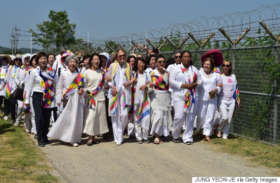 US feminist Gloria Steinem and South Korean peace activists march along a military fence at a military check point in Paju on May 24, 2015 after she crossed the border line through the demilitarised zone (DMZ) separating the two Koreas. An international group of women peace activists, led by American feminist Gloria Steinem, made a rare crossing on May 24 of one of the world's most militarised borders between North and South Korea. AFP PHOTO / JUNG YEON-JE (Photo credit should read JUNG YEON-JE/AFP/Getty Images)