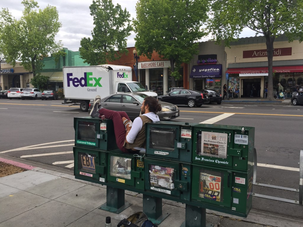 Man resting on top of newspaper vending machines